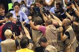 United States' Michael Phelps is surrounded by media as he kisses his son Boomer, held by his fiancee Nicole Johnson, second left, after winning the gold medal in the men's 200-meter butterfly final during the swimming competitions at the 2016 Summer Olympics, Tuesday, Aug. 9, 2016, in Rio de Janeiro, Brazil. (AP Photo/Martin Meissner)