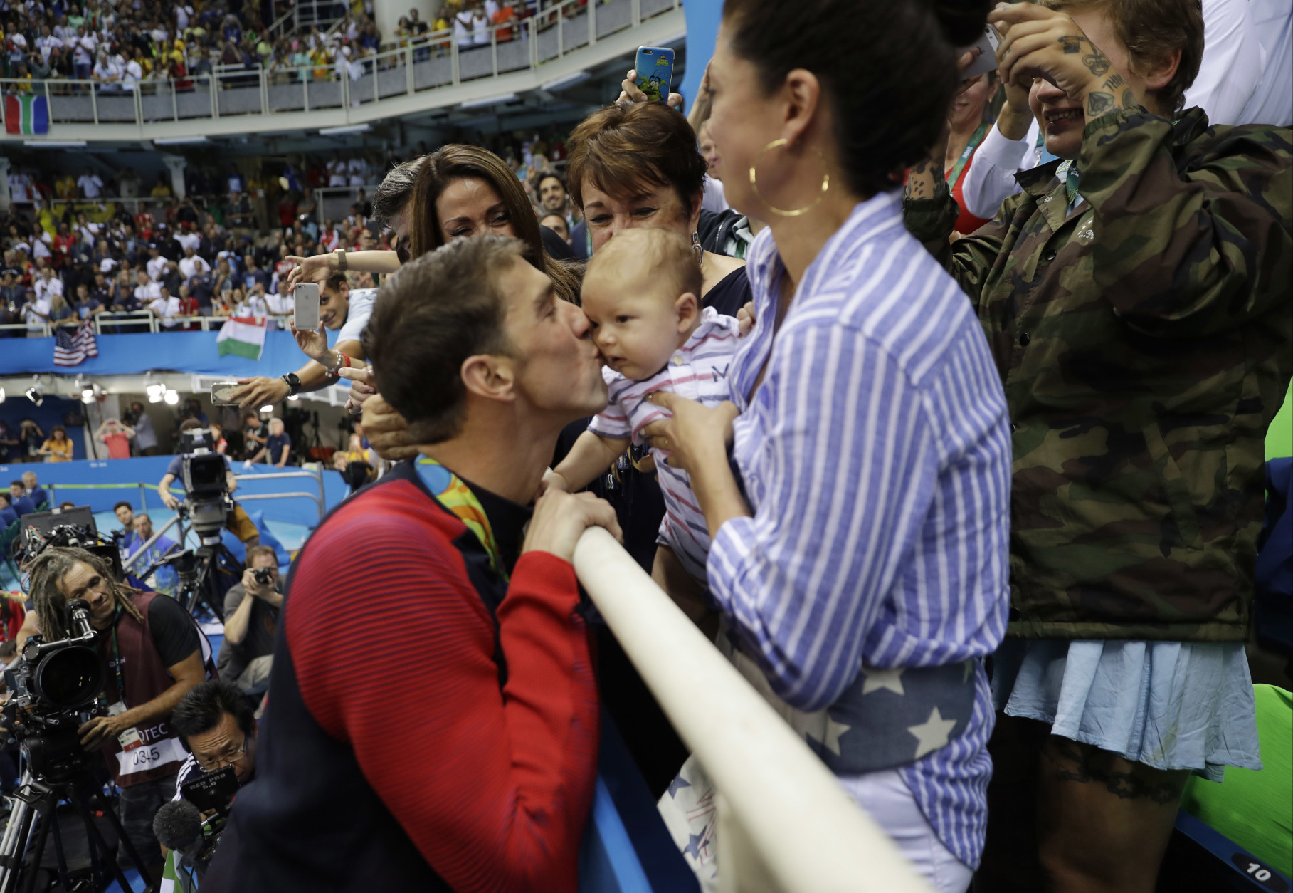 United States' Michael Phelps celebrates winning his gold medal in the men's 200-meter butterfly with his mother Debbie, fiance Nicole Johnson and baby Boomer during the swimming competitions at the 2016 Summer Olympics, Tuesday, Aug. 9, 2016, in Rio de Janeiro, Brazil. (AP Photo/Matt Slocum)