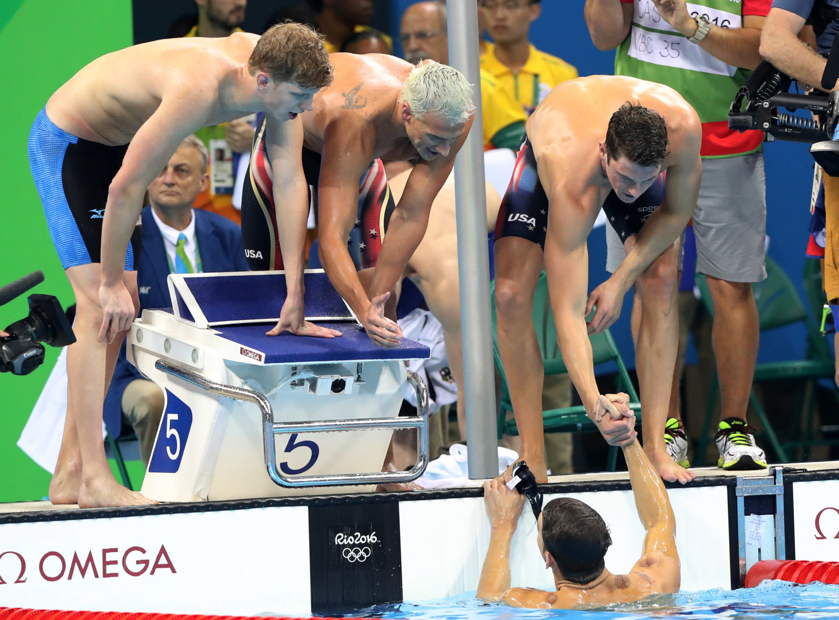 United States' Townley Haas, left, Ryan Lochte, center, and Conor Dwyer celebrate as Michael Phelps, in the pool, finishes to win the gold medal in the men's 4x200-meter freestyle final during the swimming competitions at the 2016 Summer Olympics, Tuesday, Aug. 9, 2016, in Rio de Janeiro, Brazil. (AP Photo/Lee Jin-man)