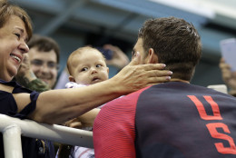 United States' Michael Phelps celebrates winning his gold medal in the men's 200-meter butterfly with his mother Debbie, fiance Nicole Johnson and baby Boomer during the swimming competitions at the 2016 Summer Olympics, Tuesday, Aug. 9, 2016, in Rio de Janeiro, Brazil. (AP Photo/David J. Phillip)