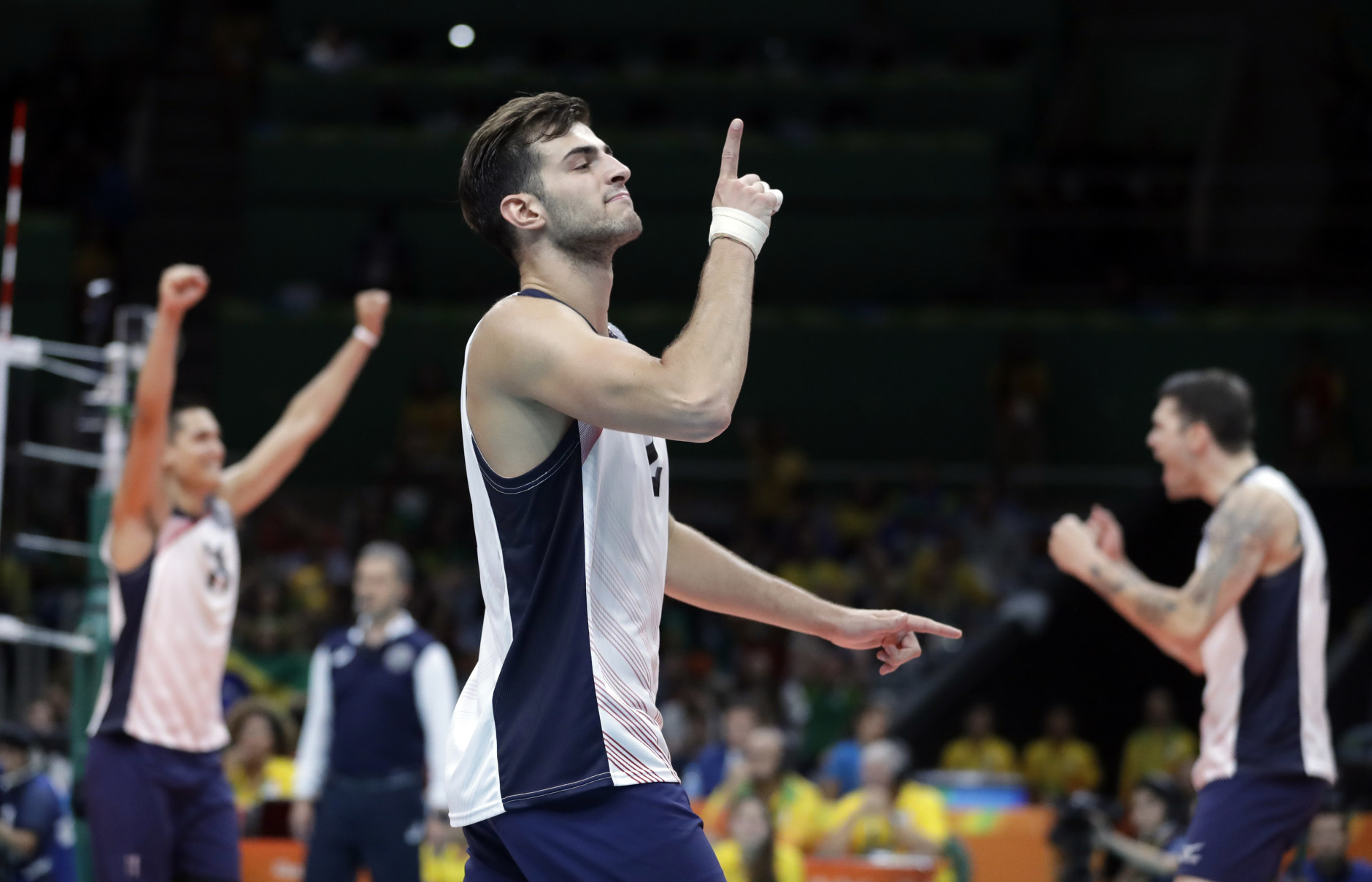 United States' Aaron Russell, center, celebrates after defeating Brazil during a men's preliminary volleyball match at the 2016 Summer Olympics in Rio de Janeiro, Brazil, Friday, Aug. 12, 2016. (AP Photo/Jeff Roberson)
