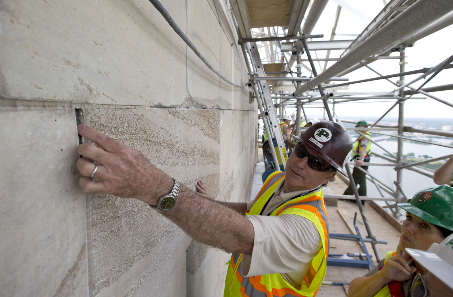 FILE - In this June 2, 2013 file photo, Bob Collie, project manager with Perini Management Services, puts his finger in a crack of the Washington Monument at the 491-foot level of the scaffolding surrounding the monument, in Washington. The monument, which sustained damage from an earthquake in August 2011, will re-open to the public on Monday, May 12, 2014. (AP Photo/Alex Brandon, File)
