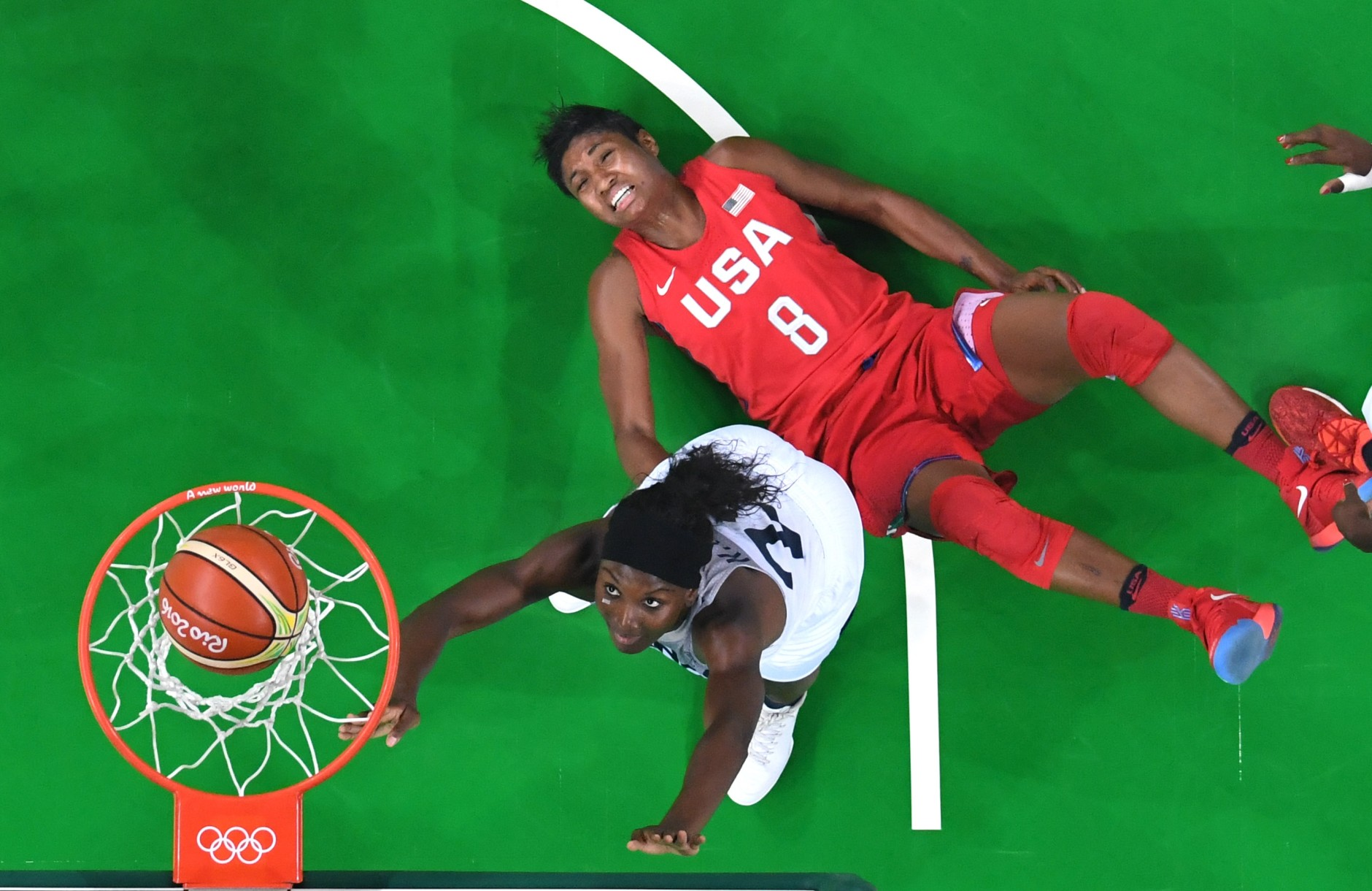 United States' Angel McCoughtry (8) falls to the floor as her shot over France's Laetitia Kamba, left, falls through the basket during a women's semifinals basketball game at the 2016 Summer Olympics in Rio de Janeiro, Brazil, Thursday, Aug. 18, 2016. (Andrej Isakovic/Pool Photo via AP)