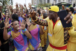 An athlete from Ghana dances with Brazilian performers at a welcoming ceremony at the 2016 Summer Olympics in Rio de Janeiro, Brazil, Wednesday, Aug. 3, 2016. (AP Photo/Robert F. Bukaty)