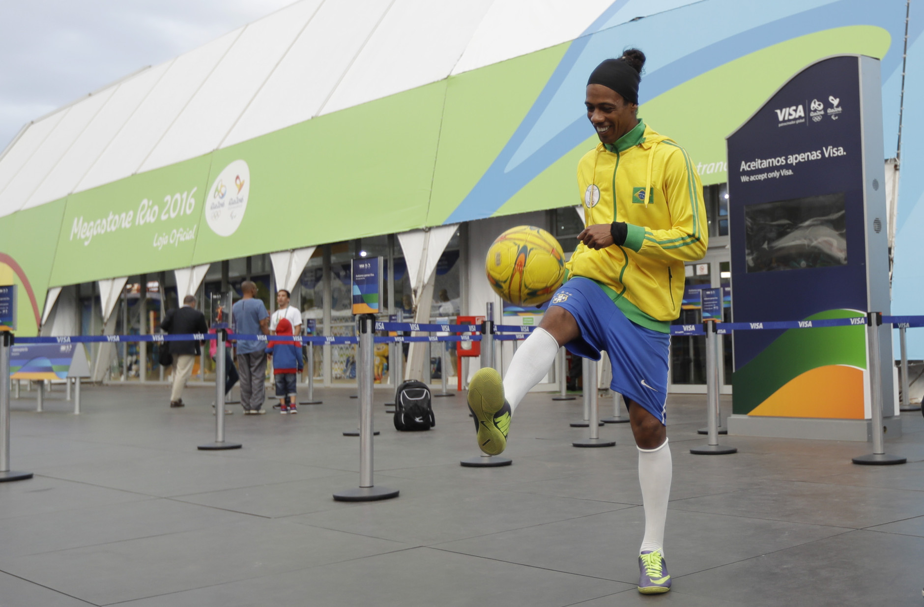 Robinson Oliveira, who works as a professional lookalike of the Brazilian soccer star Ronaldinho kicks a ball in front of a souvenir store for the 2016 Summer Olympics along Copacabana beach in Rio de Janeiro, Brazil, Wednesday, Aug. 3, 2016. The Olympics are scheduled to open Aug. 5. (AP Photo/Gregory Bull)