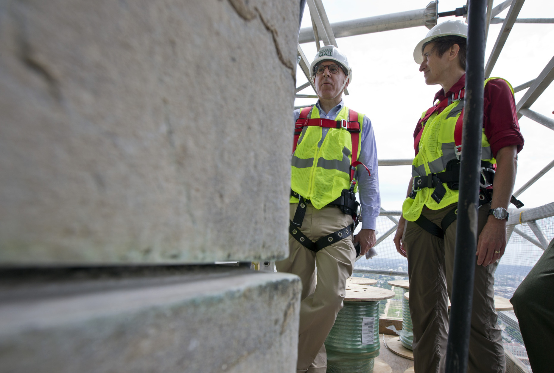 Philanthropist David Rubenstein, left, and Secretary of the Interior Sally Jewell, stand during an interview with The Associated Press at the 491-foot level of the scaffolding surrounding the Washington Monument, Sunday, June 2, 2013 in Washington. The monument has been closed since the 2011 earthquake and half of the needed repairs have been funded by a $7.5 million donation from Rubenstein. The Associated Press had a look at some of the worst damage and the preparations underway to begin making repairs. Stone by stone, engineers are reviewing cracks, missing pieces and broken mortar now that huge scaffolding has been built around the towering symbol of the nation's capital. (AP Photo/Alex Brandon)