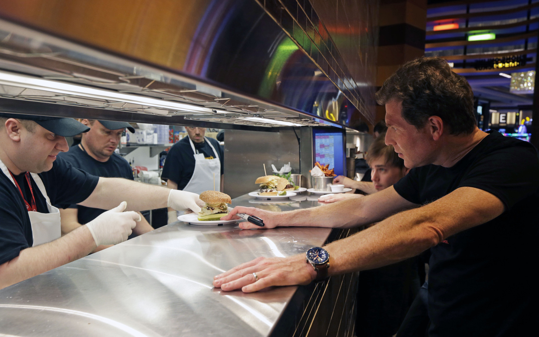 Chef Bobby Flay, right, checks an order from the kitchen at his new restaurant, Bobby's Burger Palace, opening inside Horseshoe Casino Cincinnati, Monday, March 4, 2013, in Cincinnati. The casino is set to open to the public Monday evening. March 4. (AP Photo/Al Behrman)
