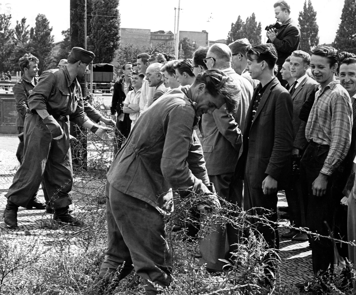East German soldiers, left, set up barbed wire barricades August , 13, 1961 at the border seperating Berlin, Germany, to restrict the travel between the eastern and western part of the German city. West Berlin citizens, right, watch the work.  (AP Photo)