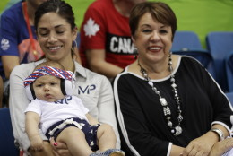 United States' Michael Phelps' son Boomer, with his fiancee Nicole Johnson and mother Debbie, wears ear protection during the swimming competitions at the 2016 Summer Olympics, Monday, Aug. 8, 2016, in Rio de Janeiro, Brazil. (AP Photo/Michael Sohn)
