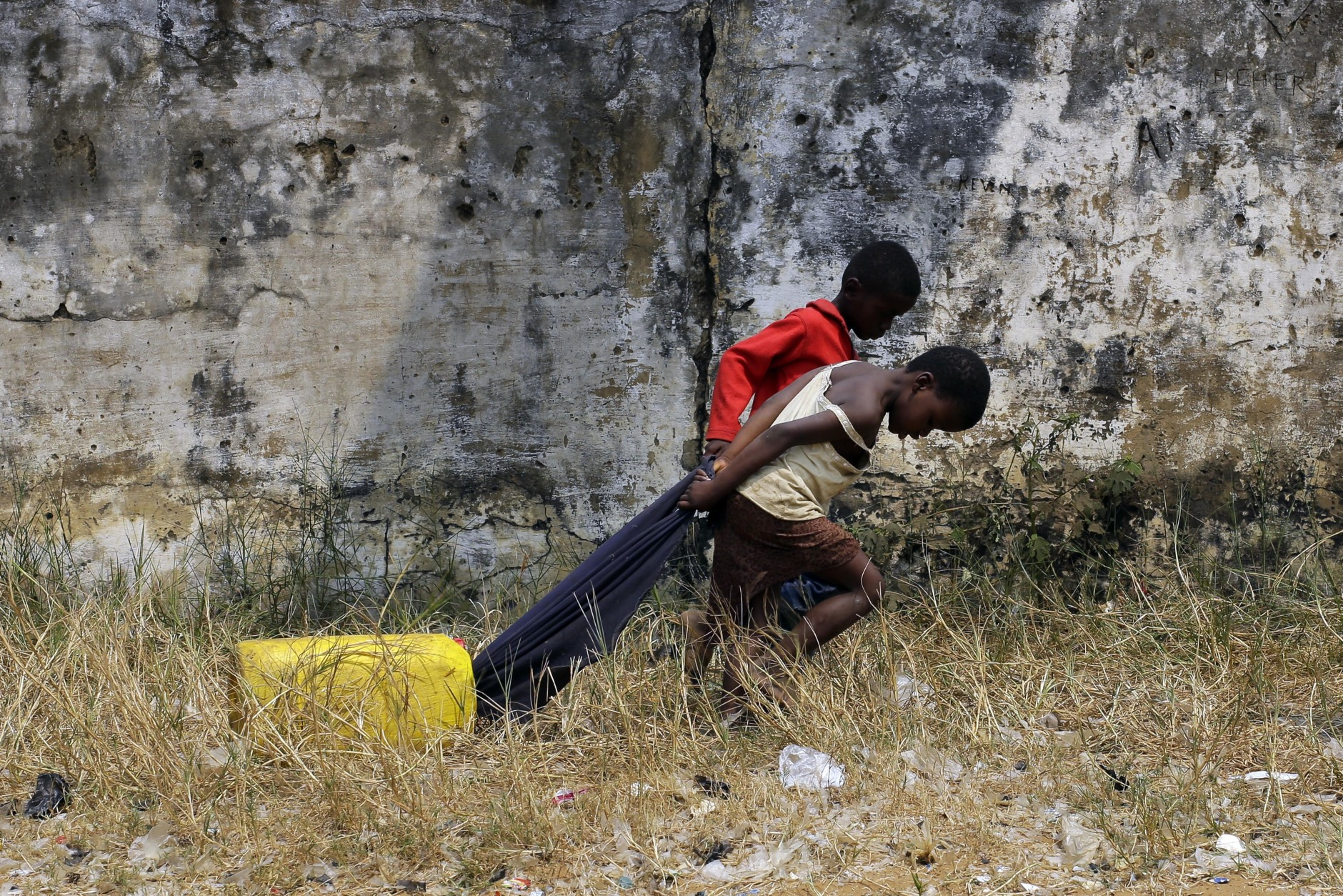 Children pull a container of water in the Kisenso district of Kinshasa, Congo, on Wednesday, July 20, 2016. There is much uncertainty about the control of yellow fever in Congo, where a surge of cases could spark further waves of the epidemic. (AP Photo/Jerome Delay)