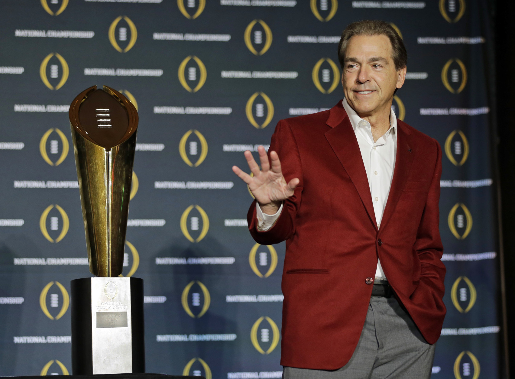FILE - In this Jan. 12, 2016, file photo, Alabama head coach Nick Saban poses with the championship trophy during a news conference for the NCAA college football playoff championship in Scottsdale, Ariz.  Saban is one national title away from matching Bear Bryant's record and, with his 65th birthday coming up on Halloween, shows no signs of slowing down. (AP Photo/David J. Phillip, File)