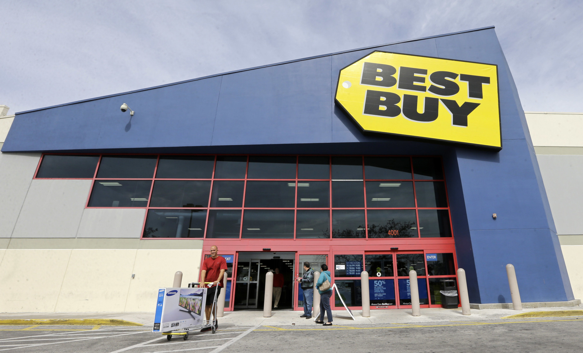 FILE - In this Tuesday, Feb. 9, 2016, file photo, a shopper carts his purchased LED TV at a Best Buy in Miami. On Tuesday, Aug. 23, Best Buy reports financial results. (AP Photo/Alan Diaz, File)