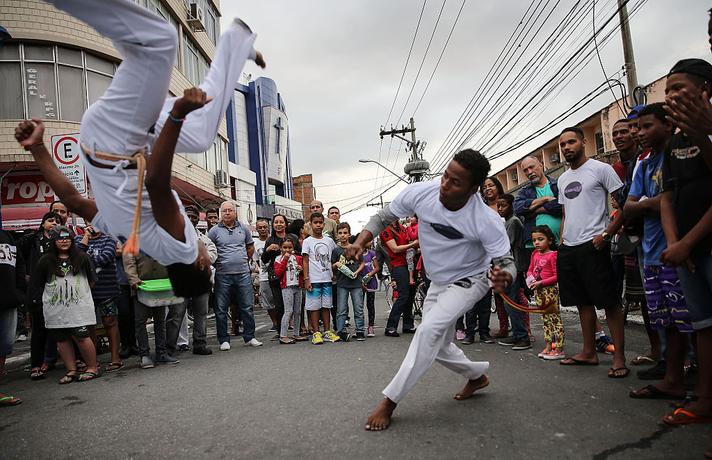 RIO DE JANEIRO, BRAZIL - AUGUST 03:  Brazilians perform capoeira, a Brazilian martial art mixing dance and music, ahead of the arrival of the Olympic torch relay in Rio's North Zone on August 3, 2016 in Rio de Janeiro, Brazil. The Rio 2016 Olympic Games commence on August 5.  (Photo by Mario Tama/Getty Images)