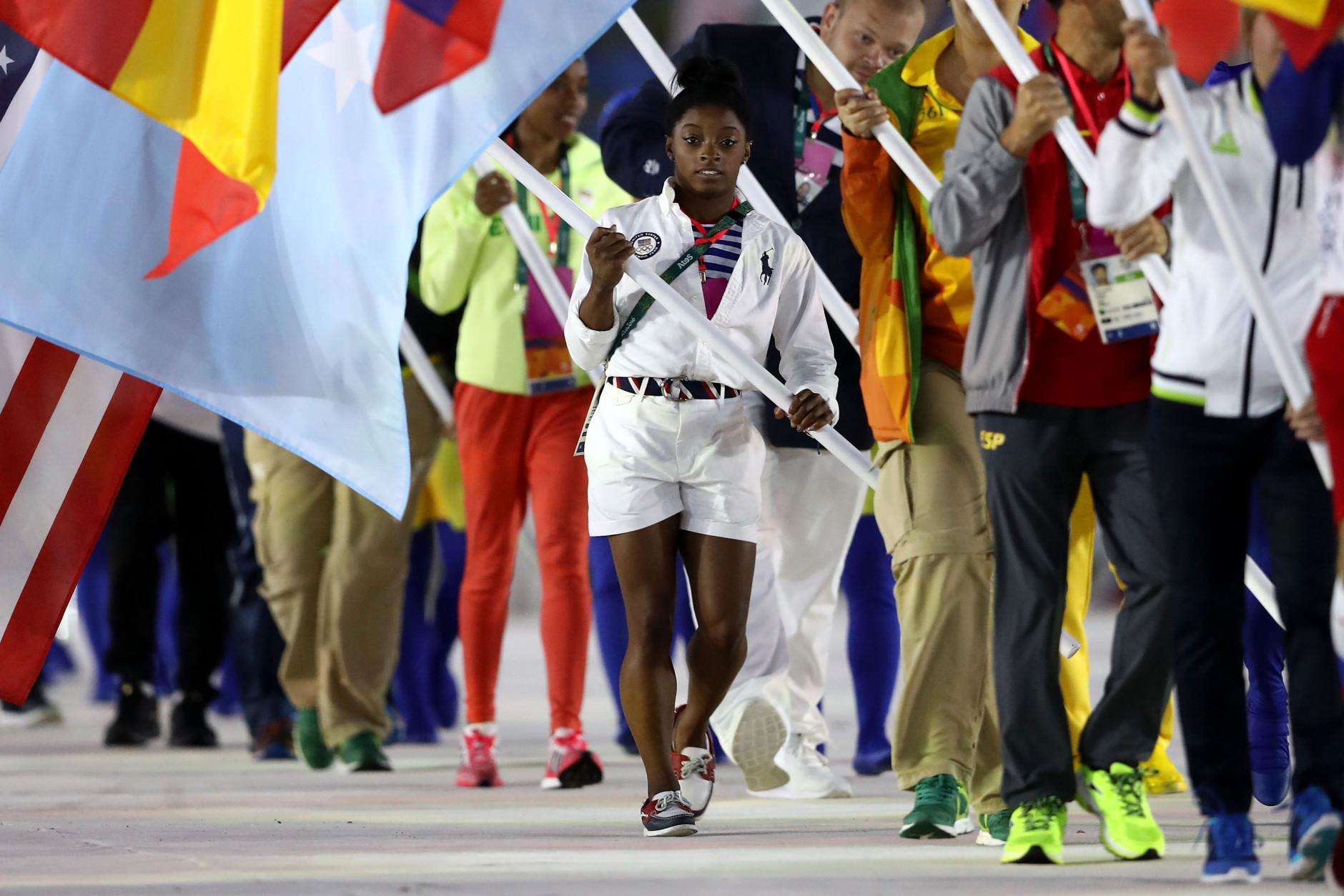 """RIO DE JANEIRO, BRAZIL - AUGUST 21:  Flag bearer Simone Biles of United States walks during the """"Heroes of the Games"""" segment during the Closing Ceremony on Day 16 of the Rio 2016 Olympic Games at Maracana Stadium on August 21, 2016 in Rio de Janeiro, Brazil.  (Photo by Ezra Shaw/Getty Images)"""