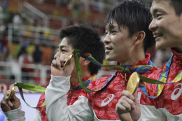 Gold medallists, from right to left, Japan's Yusuke Tanaka, Kohei Uchimura and Koji Yamamuro hold their medals during the medal ceremony for the artistic gymnastics men's team the 2016 Summer Olympics in Rio de Janeiro, Brazil, Monday, Aug. 8, 2016. (AP Photo/Julio Cortez)