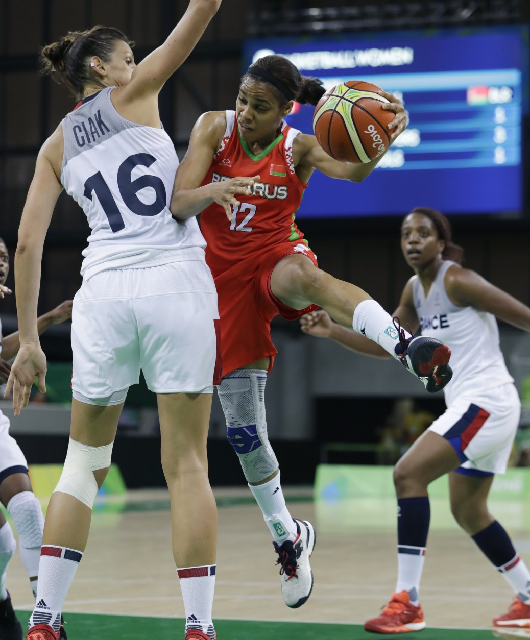 Belarus guard Lindsey Harding (12) passes around the defense of France center Helena Ciak (16) during the first half of a women's basketball game at the Youth Center at the 2016 Summer Olympics in Rio de Janeiro, Brazil, Sunday, Aug. 7, 2016. (AP Photo/Carlos Osorio)