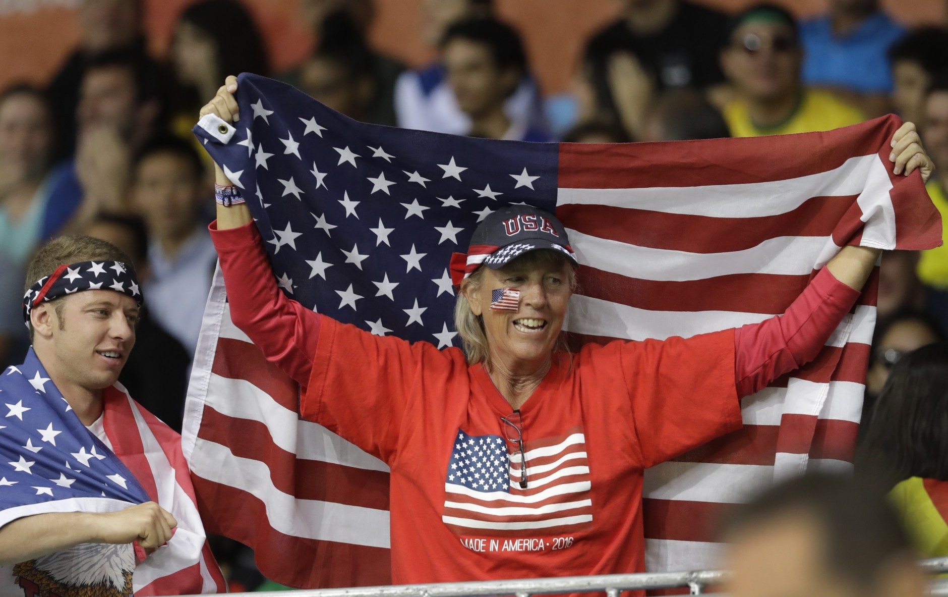 A fan bearing a United States flag is seen during the second half of a women's basketball game between the United States and Spain at the Youth Center at the 2016 Summer Olympics in Rio de Janeiro, Brazil, Monday, Aug. 8, 2016. (AP Photo/Carlos Osorio)