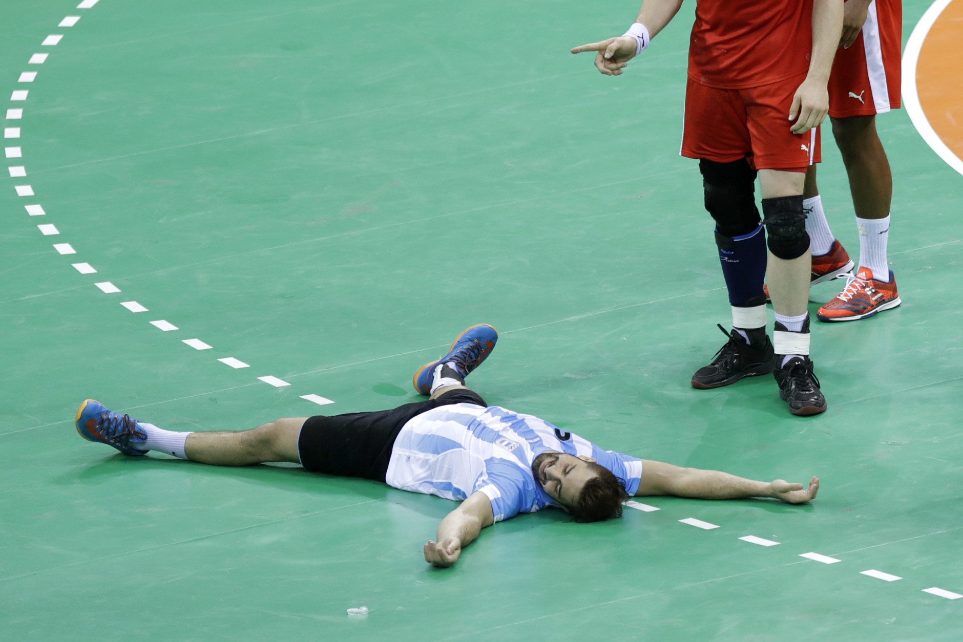 Argentina's Federico Pizarro lies on the ground after missing to score a penalty besides Denmark's Rene Toft Hansen during the men's preliminary handball match between Denmark and Argentina at the 2016 Summer Olympics in Rio de Janeiro, Brazil, Sunday, Aug. 7, 2016. (AP Photo/Matthias Schrader)