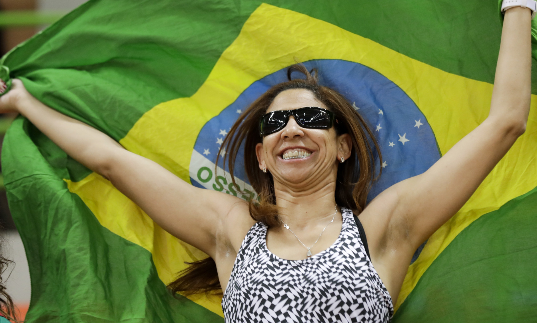 A fan waves a Brazilian flag before the women's preliminary handball match between Norway and Brazil at the 2016 Summer Olympics in Rio de Janeiro, Brazil, Saturday, Aug. 6, 2016. (AP Photo/Ben Curtis)