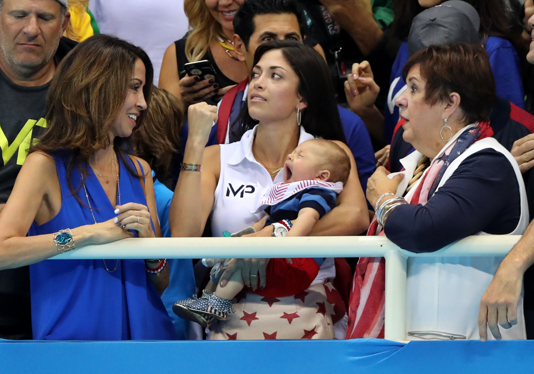 FILE - In this Aug. 13, 2016, file photo, Nicole Johnson, fiance of United States' Michael Phelps, holds their baby Boomer, as she stands along with Phelps' mother Debbie and sister during the men's 4 x 100-meter medley relay final during the swimming competitions at the 2016 Summer Olympics, in Rio de Janeiro, Brazil. Phelps can't wait to return home to Arizona and settle into a retirement of changing diapers, bottle-feeding and watching Boomer grow. (AP Photo/Lee Jin-man, File)