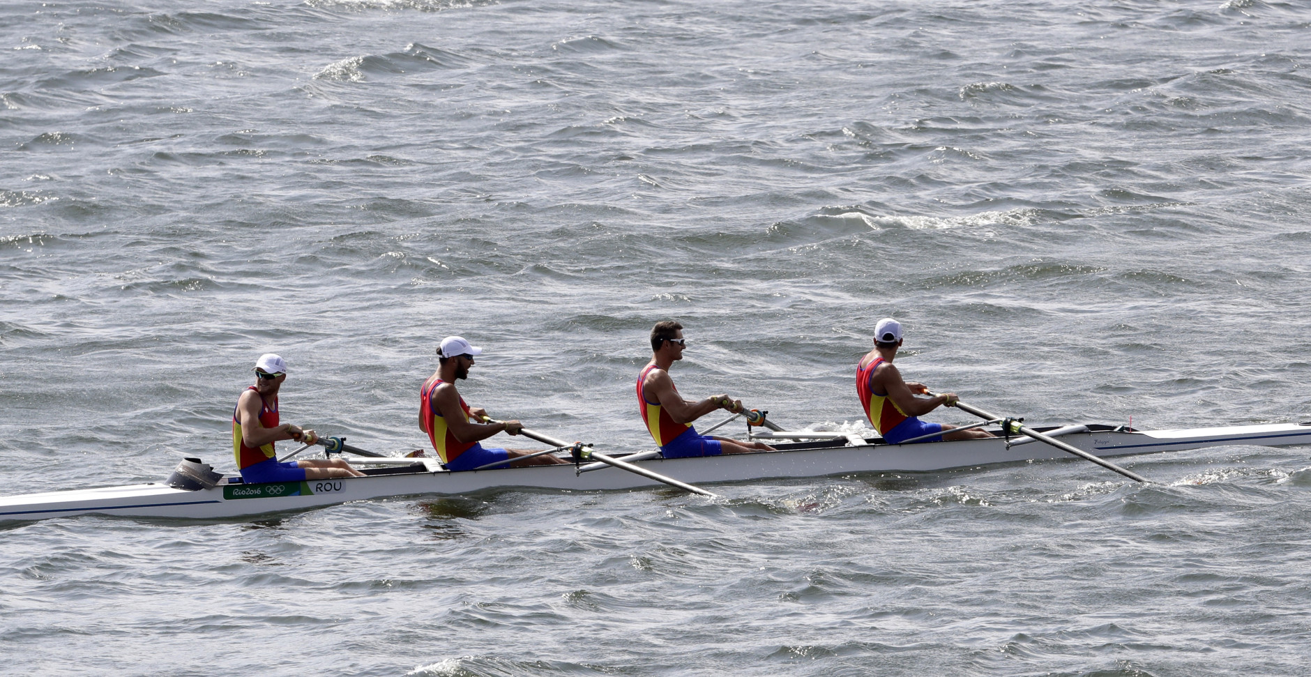 A team from Romania who were training return to shore after high winds postponed their competition for the day at the 2016 Summer Olympics in Rio de Janeiro, Brazil, Sunday, Aug. 7, 2016. (AP Photo/Matt York)