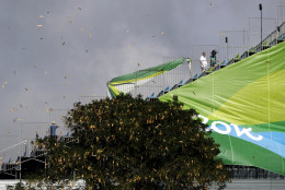 Debris is blown through the grandstands by high winds as spectators exit after the rowing competition was postponed for the day at the 2016 Summer Olympics in Rio de Janeiro, Brazil, Sunday, Aug. 7, 2016. (AP Photo/Luca Bruno)