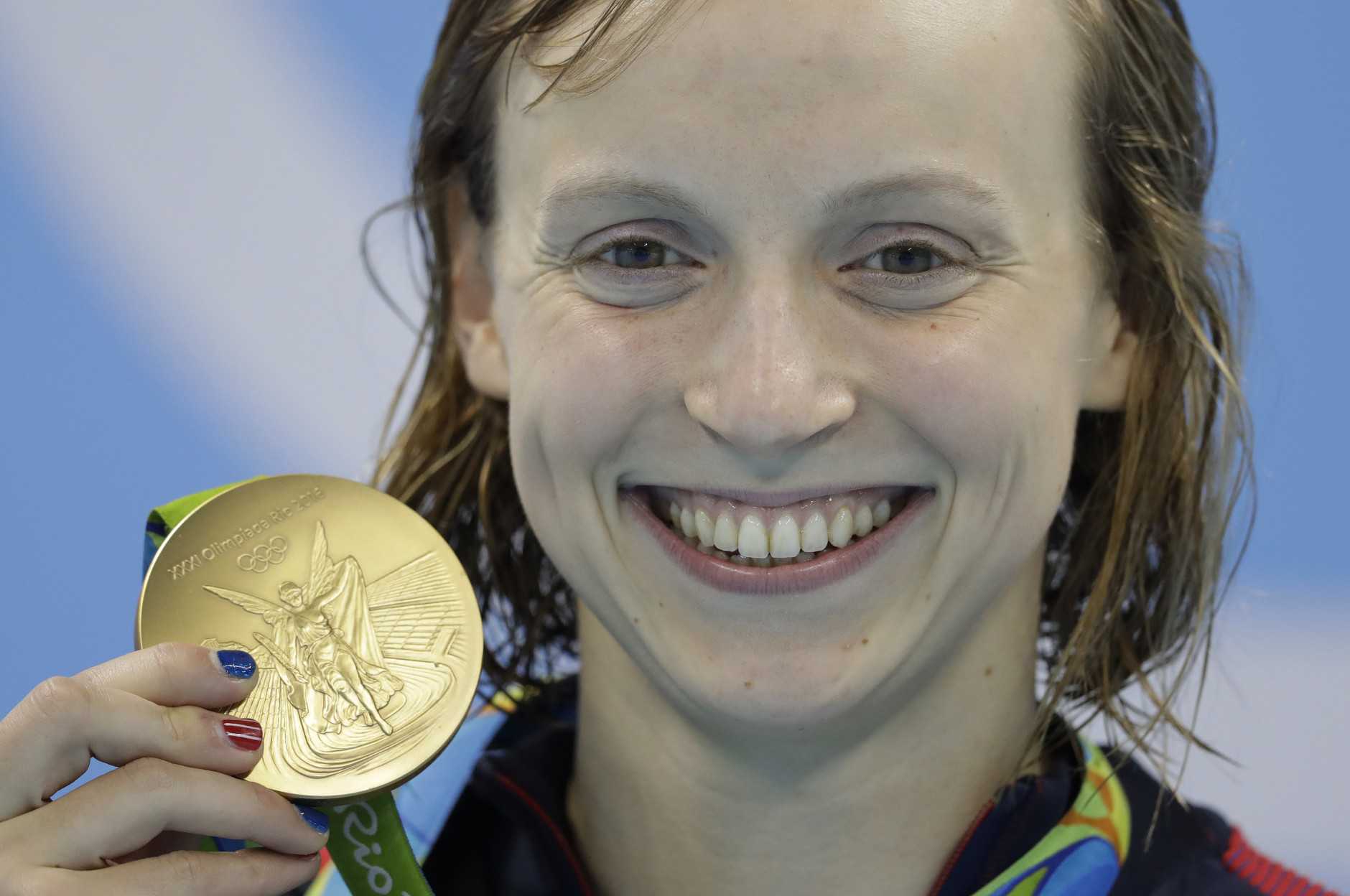 United States' Katie Ledecky shows off her gold medal after setting a new world record in the women's 400-meter freestyle final during the swimming competitions at the 2016 Summer Olympics, Monday, Aug. 8, 2016, in Rio de Janeiro, Brazil. (AP Photo/Michael Sohn)