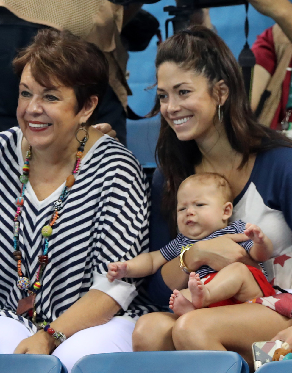 The family of United States' Michael Phelps, mother Debbie, left, and his fiance Nicole Johnson holding their baby Boomer watch the swimming competitions at the 2016 Summer Olympics, Monday, Aug. 8, 2016, in Rio de Janeiro, Brazil. (AP Photo/Lee Jin-man)