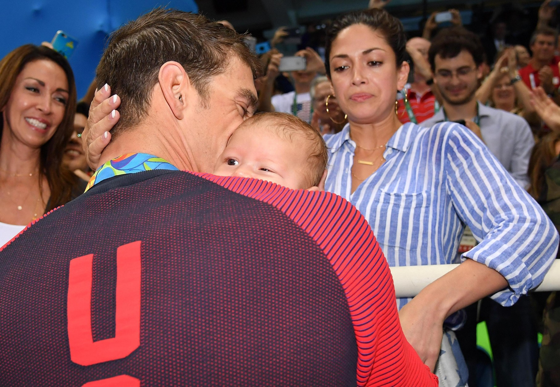 United States' Michael Phelps celebrates winning his gold medal in the men's 200-meter butterfly with his fiancee Nicole Johnson and baby Boomer during the swimming competitions at the 2016 Summer Olympics, Tuesday, Aug. 9, 2016, in Rio de Janeiro, Brazil. (Ettore Ferrari/ANSA via AP)