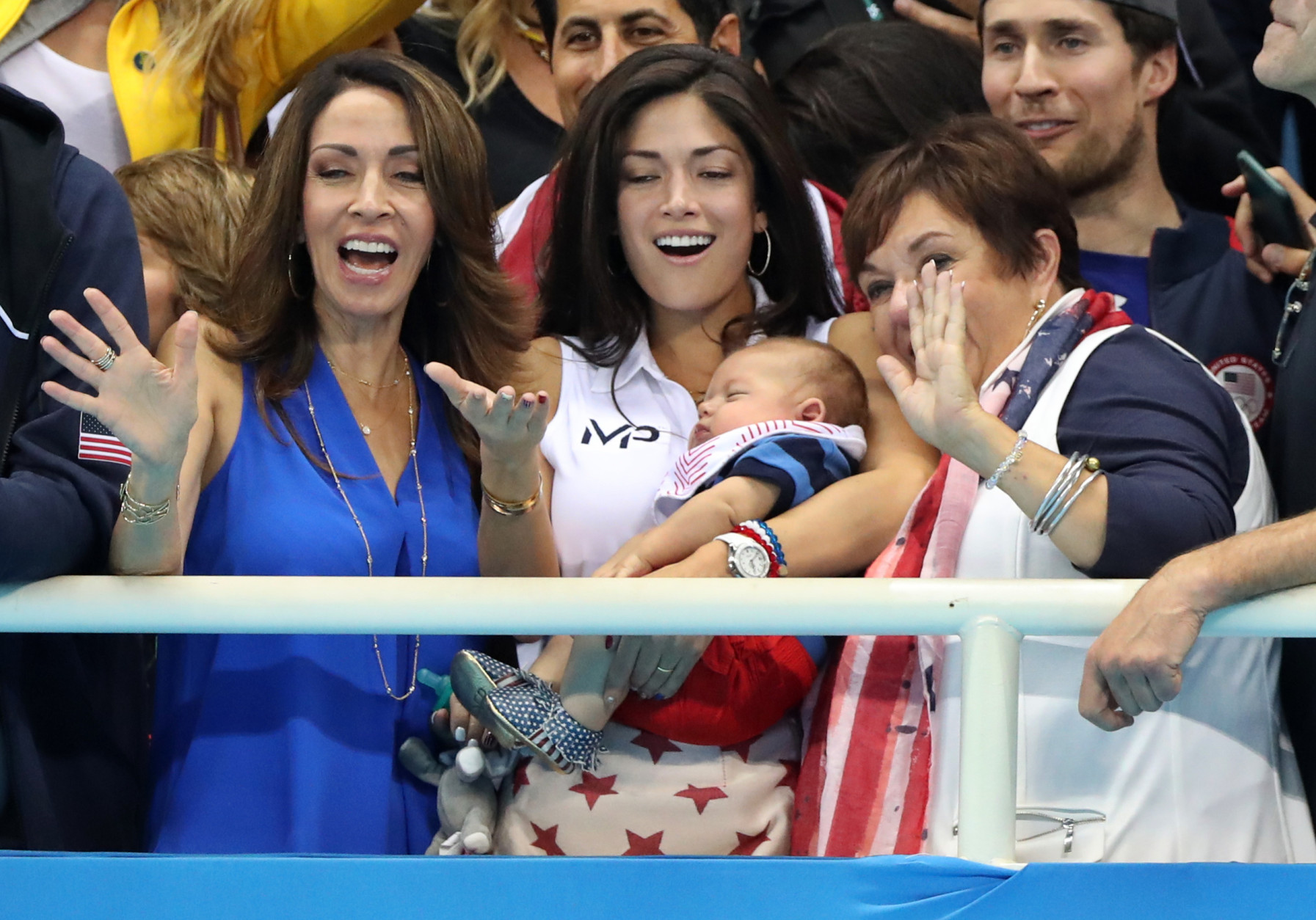 Nicole Johnson, fiance of United States' Michael Phelps, holds their baby Boomer, as she cheers along with Phelps' mother Debbie and sister during the men's 4 x 100-meter medley relay final during the swimming competitions at the 2016 Summer Olympics, Saturday, Aug. 13, 2016, in Rio de Janeiro, Brazil. (AP Photo/Lee Jin-man)