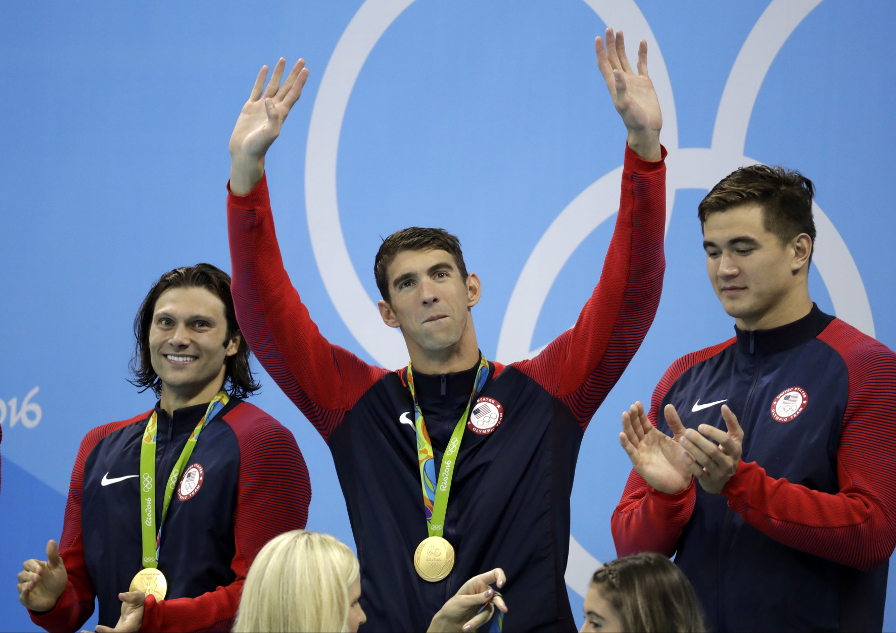 United States' Michael Phelps waves as teammates Cody Miller, left, and Nathan Adrian look on during the medal ceremony for the men's 4 x 100-meter medley relay final during the swimming competitions at the 2016 Summer Olympics, Sunday, Aug. 14, 2016, in Rio de Janeiro, Brazil. (AP Photo/Rebecca Blackwell)