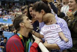 FILE - In this Aug. 9, 2016, file photo, United States' Michael Phelps celebrates winning his gold medal in the men's 200-meter butterfly with his fiance Nicole Johnson and baby Boomer during the swimming competitions at the 2016 Summer Olympics, in Rio de Janeiro, Brazil. Phelps can't wait to return home to Arizona and settle into a retirement of changing diapers, bottle-feeding and watching Boomer grow.  (AP Photo/Matt Slocum, File)