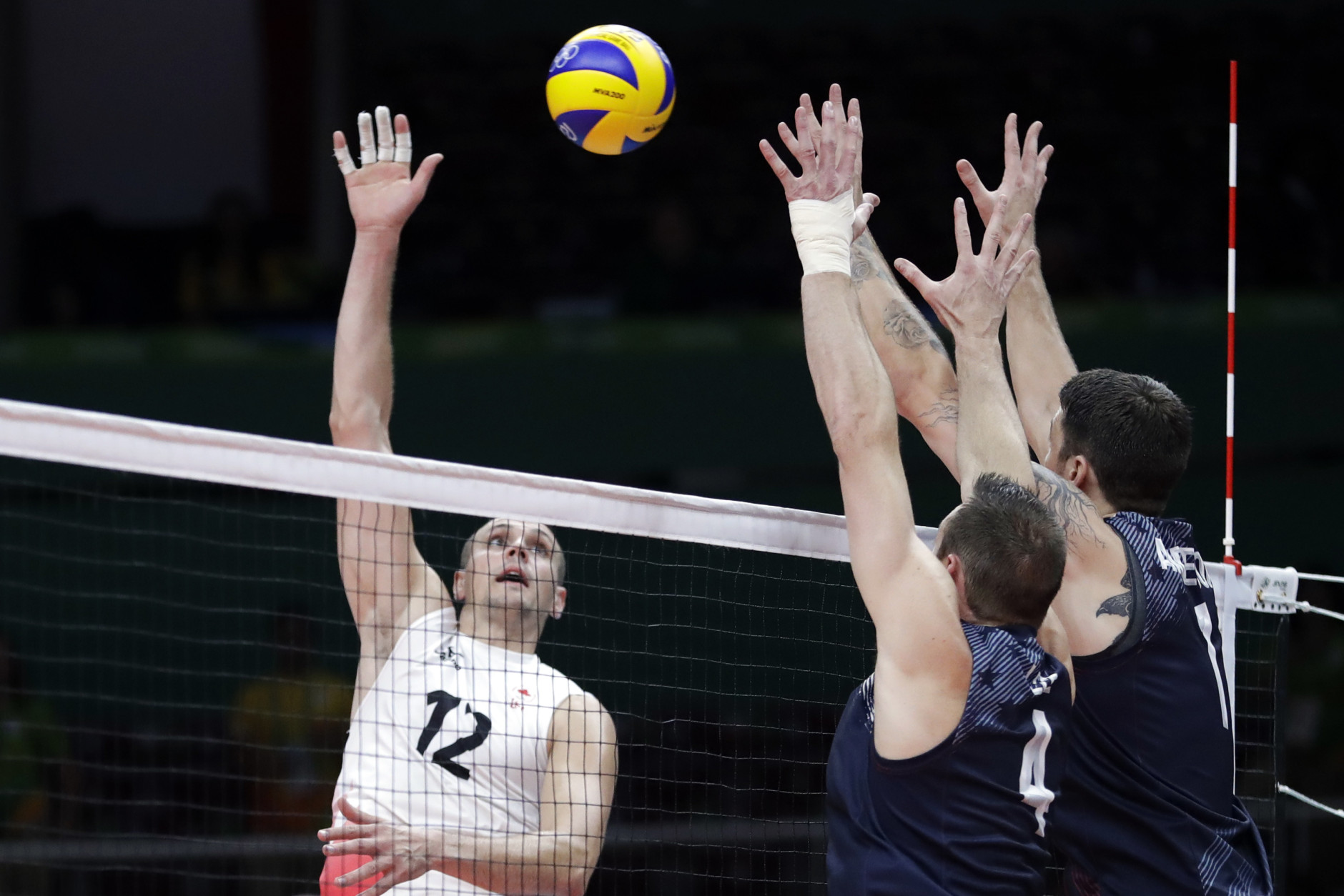 Canada's Gavin Schmitt (12) spikes the ball as United States' David Lee, center, and Matthew Anderson, right, attempt to block during a men's preliminary volleyball match at the 2016 Summer Olympics in Rio de Janeiro, Brazil, Sunday, Aug. 7, 2016. (AP Photo/Jeff Roberson)