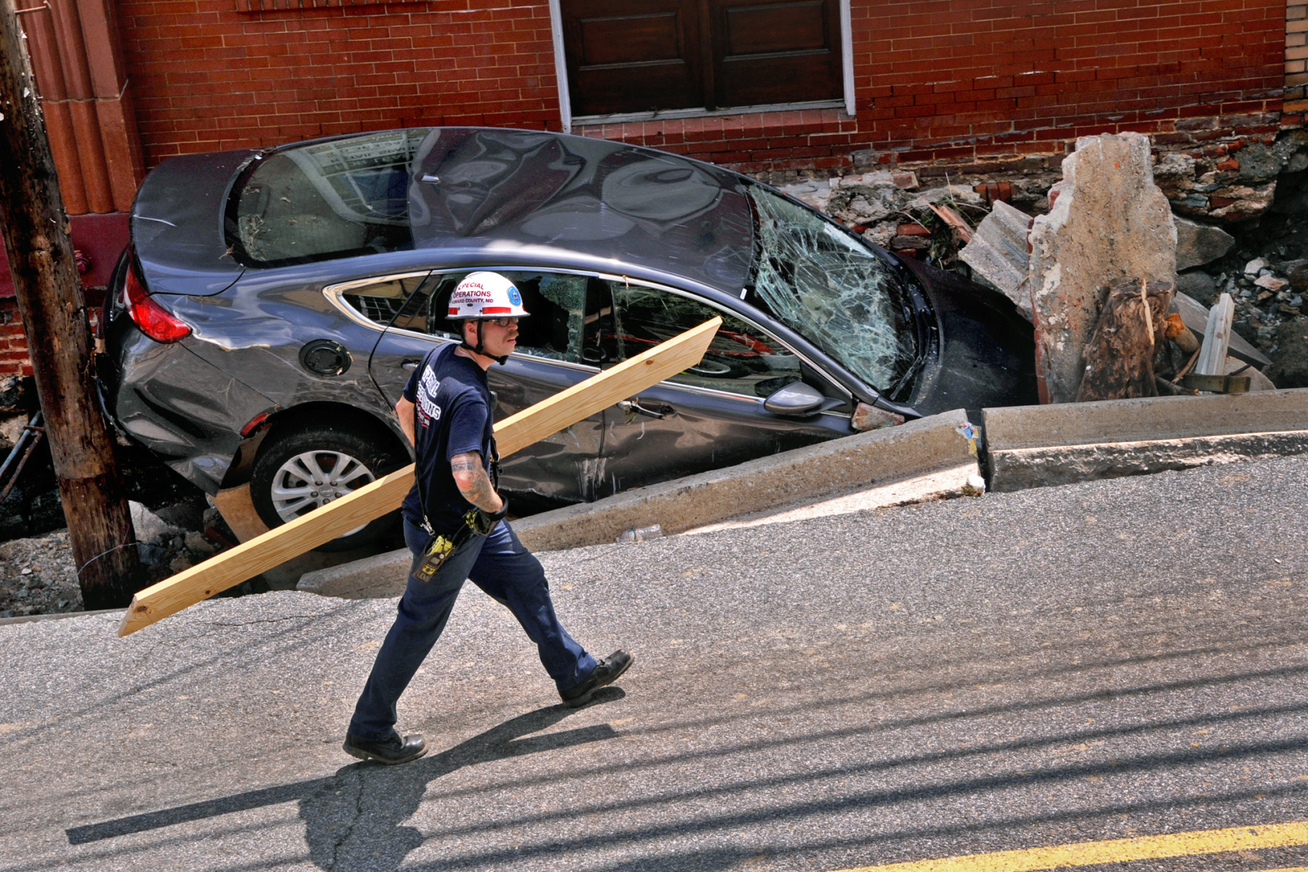 A worker carries lumber to shore up one of the stores on Main Street after the sidewalk caved in due to overnight flooding in Ellicott City, Md., Sunday, July 31, 2016. Historic, low-lying Ellicott City, Maryland, was ravaged by floodwaters Saturday night, killing a few people and causing devastating damage to homes and businesses, officials said. (Amy Davis/The Baltimore Sun via AP)
