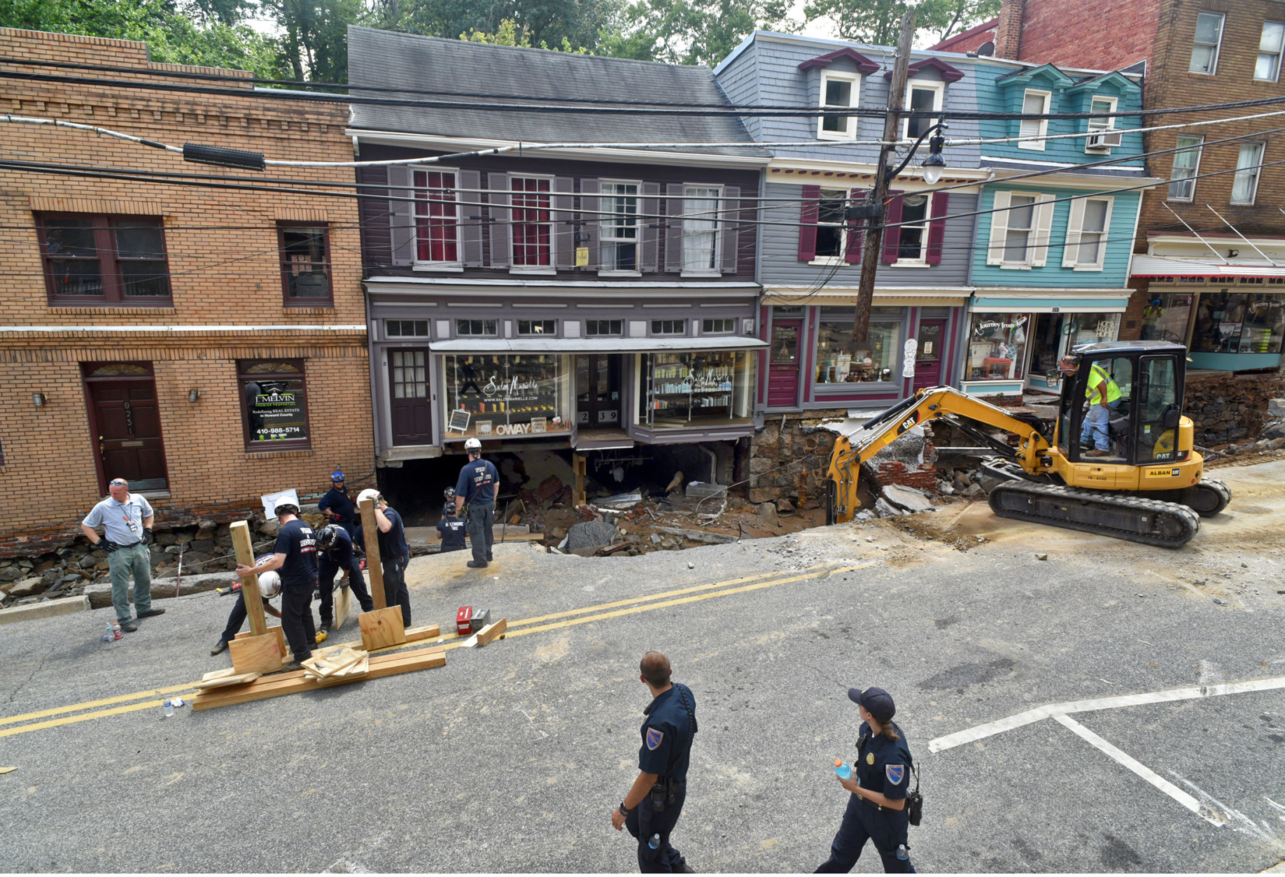 Recovery and cleanup is underway on historic Main Street after the sidewalk caved in due to overnight flooding in Ellicott City, Md., Sunday, July 31, 2016. Historic, low-lying Ellicott City, Maryland, was ravaged by floodwaters Saturday night, killing a few people and causing devastating damage to homes and businesses, officials said. (Amy Davis/The Baltimore Sun via AP)