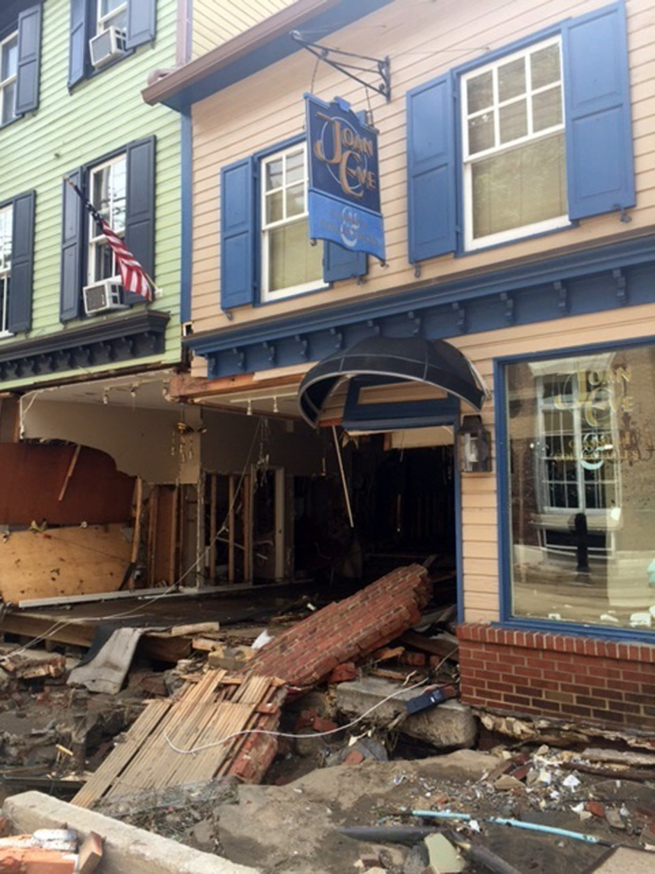 Damage along Main Street in historic Ellicott City, Md., is viewed Monday, Aug. 1, 2016, after the city was ravaged by floodwaters Saturday night, killing two people and causing devastating damage to homes and businesses, officials said. Virtually every home or business along  the street sustained at least some damage, and the cost of repairs could reach the hundreds of millions of dollars, said Howard County Executive Allan Kittleman. (AP Photo/Juliet Linderman)