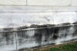This photo shows the black growth that began coating the sides of the Jefferson Memorial more than a decade ago. The biofilm - a combination of bacteria, fungi and algae, has spread more rapidly in recent years and this week the National Park Service applied various chemical agents to a section of the marble to see if any would remove the film. (WTOP/Nick Iannelli)