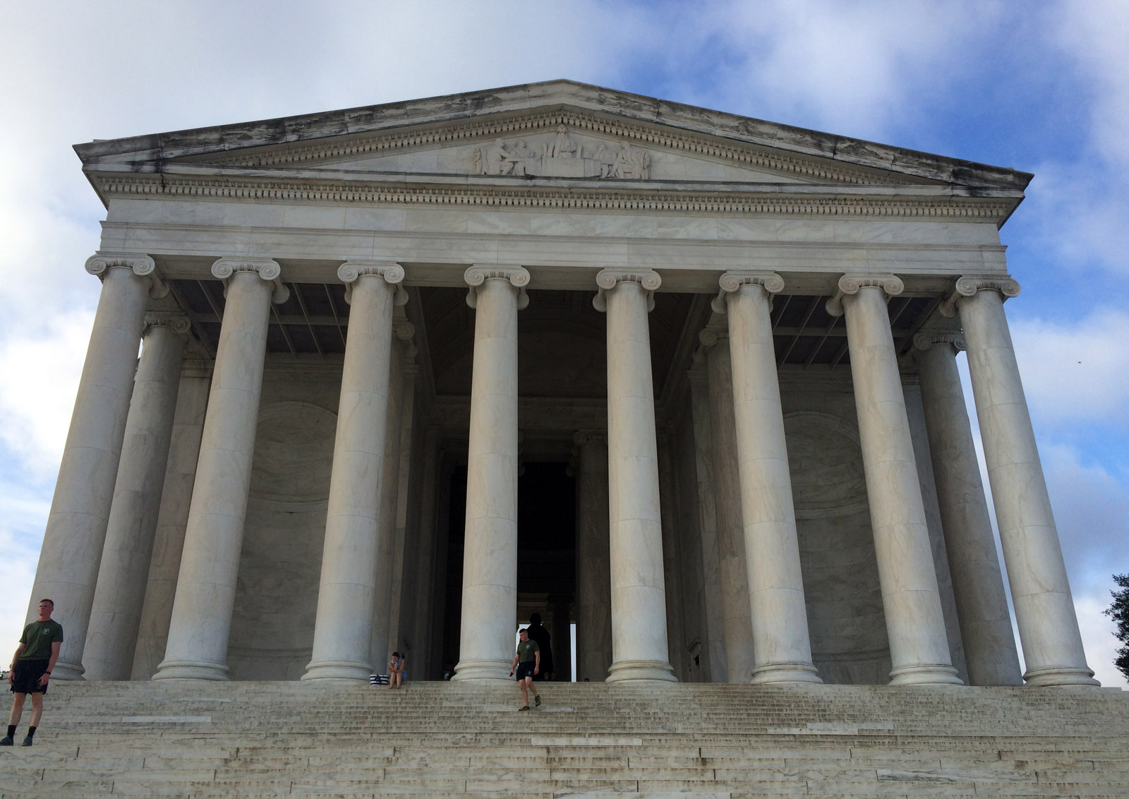A biofilm has blackened sections of the roof line of the Jefferson Memorial. The National Park Service describes the film as a combination of bacteria, fungi and algae growing on the marble of the landmark.  (WTOP/Nick Iannelli)