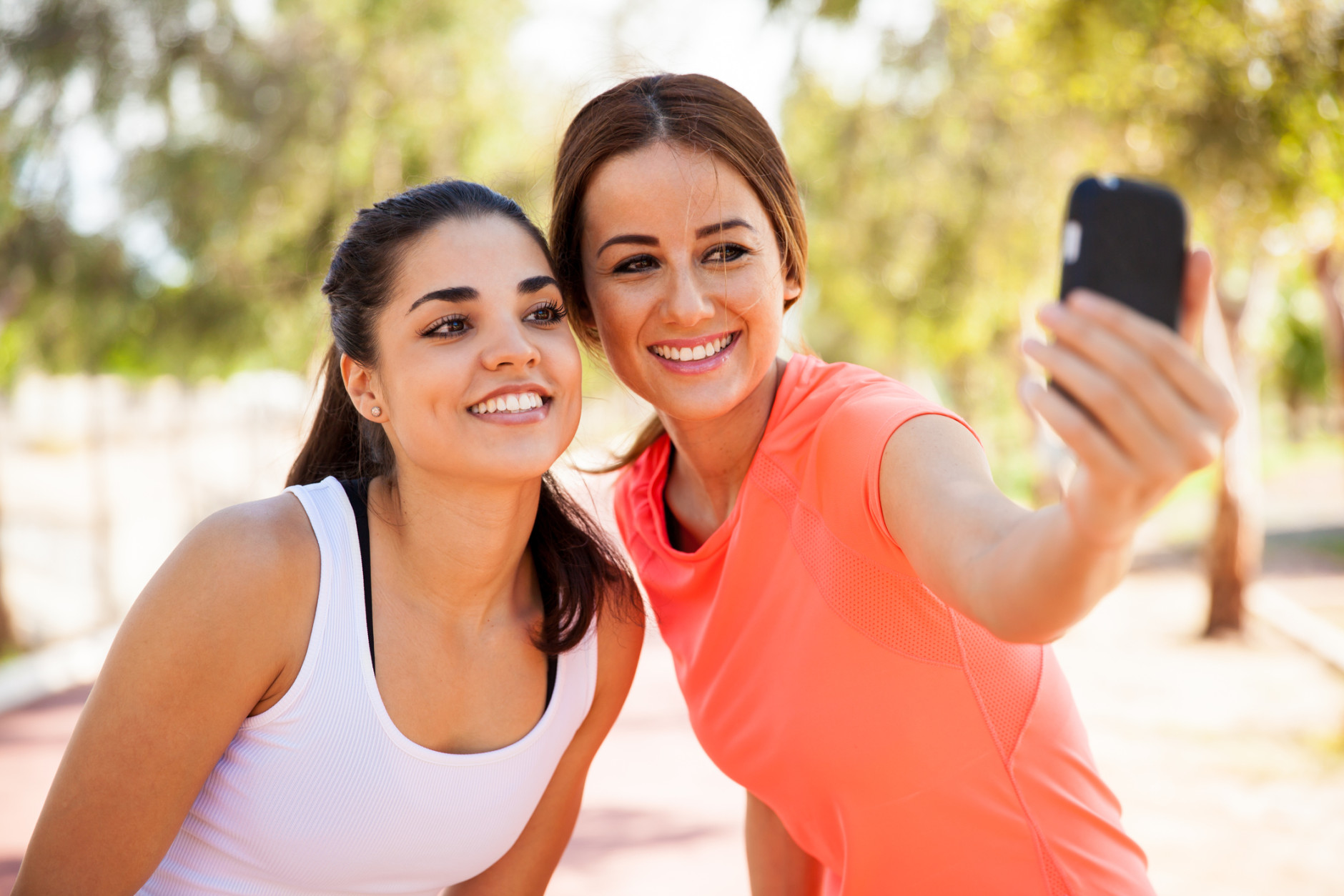 Beautiful girls taking a selfie with a smart phone before going for a run outdoors