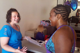Amanda Holliday, at left, speaks to a participant during a Zumbathon fundraiser in Takoma Park, Md. on Sunday, Aug. 28, 2016. Holliday says the event will raise money for the victims of the explosion at Flower Branch Apartments in Silver Spring, Md. (WTOP/Katy Stewart)
