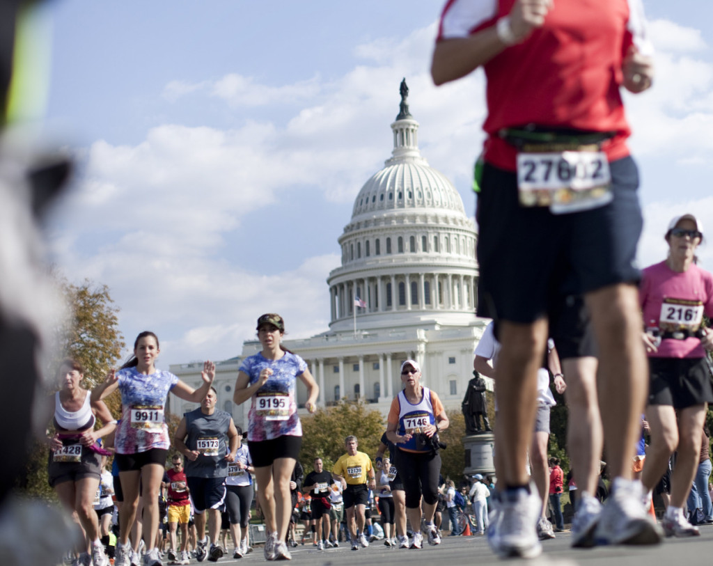 WASHINGTON - OCTOBER 31:  Runners pass the US Capitol Building on Capitol Hill during the Marine Corps Marathon October 31, 2010 in Washington, DC.  Event organizers have requested increased security at the annual 26.2 mile race after the National Museum of the Marine Corps was shot at twice this month by the same weapon used in similar acts at the Pentagon and a vacant Marine Corps recruiting station in Chantily, Virginia.  (Photo by Brendan Smialowski/Getty Images)