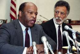 Reps. John Lewis, D-Ga., left, Ron Dellums, D-Calif., right, face reporters on Capitol Hill Sunday, Aug. 13, 1989 where they discuss the reported finding of a plane which carried Rep. Mickey Leland, D-Texas, and others aboard in Ethiopia. U.S. officials said no survivors were found. (AP Photo/Doug Mills)