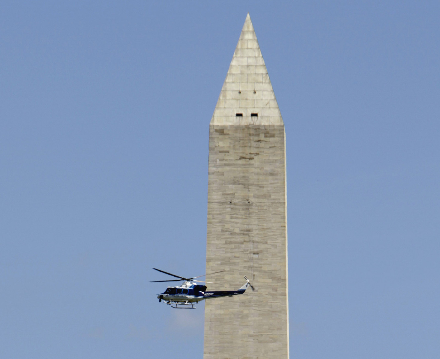 In this file photo, a U.S. Park Service helicopter flies in front of the Washington Monument in Washington, on Aug. 23, 2011, after it was evacuated following an earthquake in the Washington area. White marble and mortar on the 555-foot obelisk cracked and shook loose during the quake. Repairs to the stone cost $15 million but didn't address the elevator that takes tourists up to the observation deck inside. National Park Service officials believe that damage from the quake is likely contributing to ongoing mechanical problems with the elevator. (AP Photo/Jacquelyn Martin)