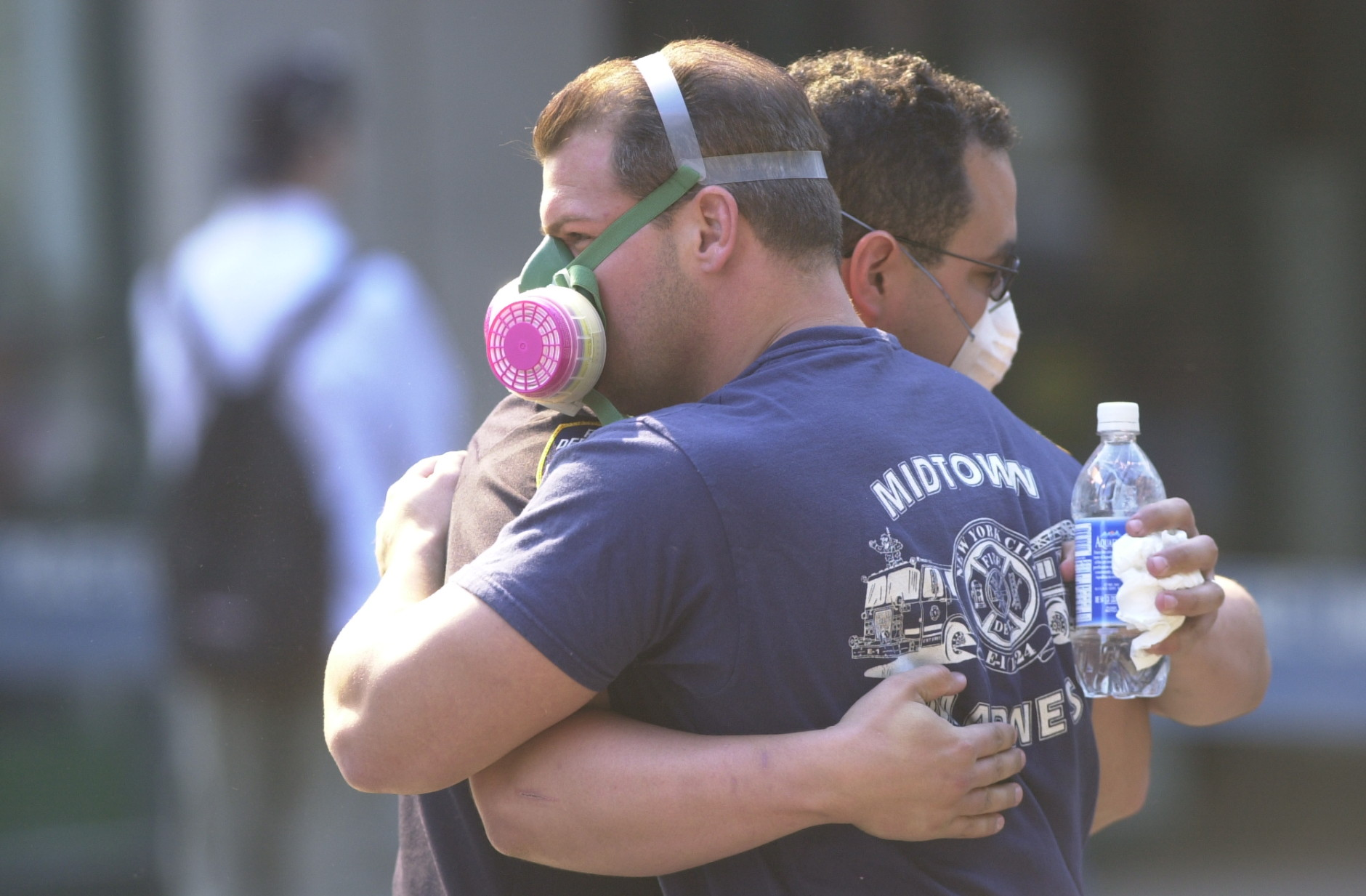 Two ground zero emergency workers hug on Sept. 13, 2001 after the September 11 terrorist attacks on the World Trade Center in New York City.(AP Photo/Lawrence Jackson)