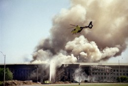 FILE - In this Sept. 11, 2001 file photo, a helicopter flies over the Pentagon in Washington as smoke billows over the building. Partial remains of several 9/11 victims were incinerated by a military contractor and sent to a landfill, a government report said Tuesday, Feb. 28, 2012, in the latest of a series of revelations about the Pentagon's main mortuary for the war dead. The terrorist-hijacked airliner that slammed into the west side of the Pentagon killed 184 people. (AP Photo/Heesoon Yim, File)