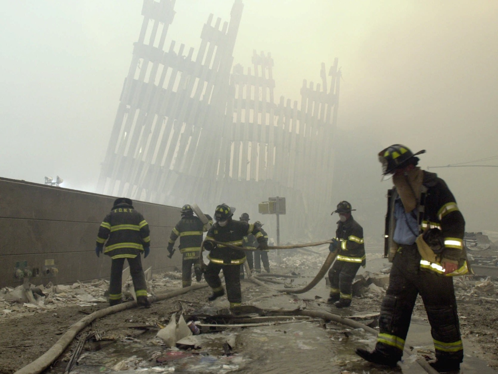 THEN-- With the skeleton of the World Trade Center twin towers in the background, New York City firefighters work amid debris on Cortlandt St. after the terrorist attacks of Tuesday, Sept. 11, 2001.  (AP Photo/Mark Lennihan)