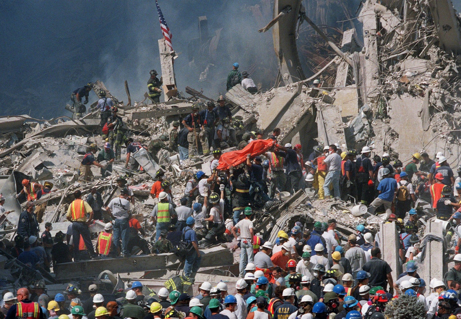 Emergency personnel carry an orange body bag with the remains of a victim of the World Trade Center crash, Thursday, Sept. 13, 2001. Two hijacked airliners crashed into the towers of the World Trade Center on Tuesday, Sept. 11, destroying both buildings. (AP Photo/Bill Farrington)