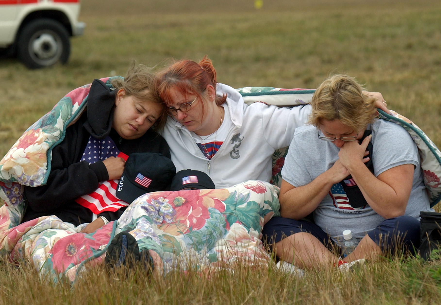 From left, Shannon Barry, Lisa Starr and Michelle Wagner, all of Hershey, Pa., react as they listen to a memorial service for victims of Flight 93 near Shanksville, Pa., Wednesday, Sept. 11, 2002. President Bush will lay a wreath at the crash site later in the day to mark the anniversary of the terrorist attacks. (AP Photo/Julie Jacobson)
