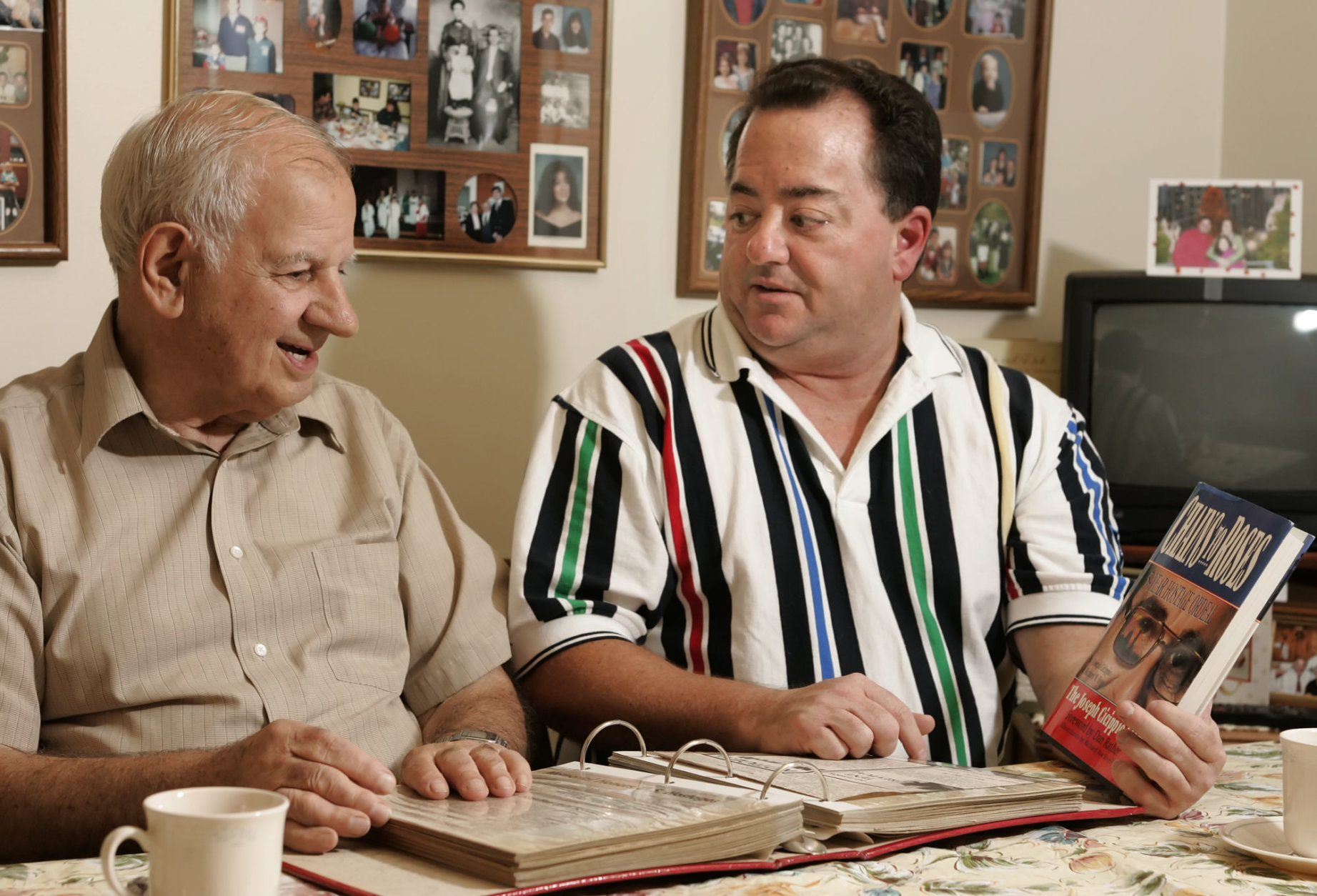 Thomas Cicippio, left, brother of Joseph Cicippio, and David Cicippio, Joseph's son, sit in Thomas' Norristown, Pa., home Wednesday, Oct. 12, 2005. The two are among the relatives of Joseph Cicippio, a former U.S. hostage held in Lebanon, who were awarded $91 million by a U.S. judge for emotional distress in a lawsuit filed against the Islamic Republic of Iran. David Cicippio holds a copy of his father's book, which describes his 1986-1991 captivity. (AP Photo/George Widman)