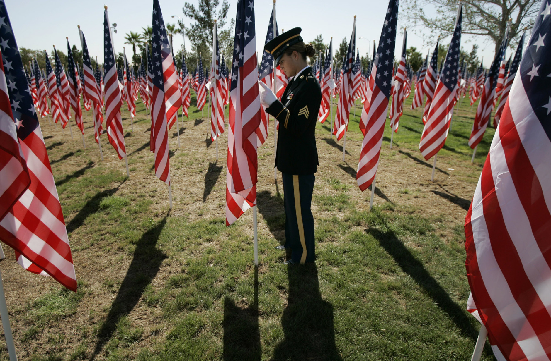 Sgt. Neomi Raap, an honor guard member of the Nevada Army National Guard, reads a name attached to a flag while visiting a 9/11 memorial in Las Vegas on Monday, Sept. 11, 2006. Palm Mortuary of Las Vegas put up 2,996 U.S. flags honoring the people killed five years ago in the terrorist attacks. (AP Photo/Laura Rauch)